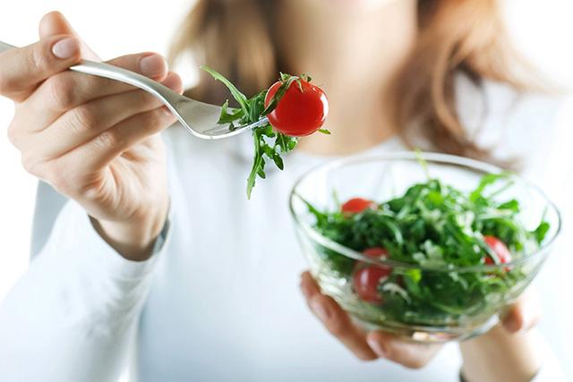水菜のサラダを食べる女性