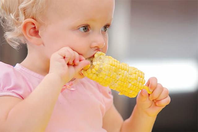 とうもろこしを食べる子供