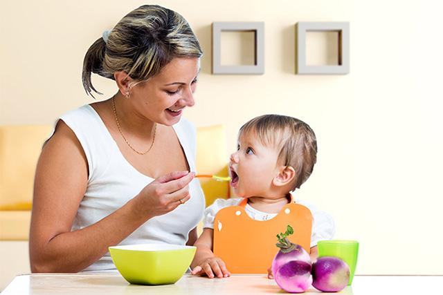 子供に野菜を食べさせる母親