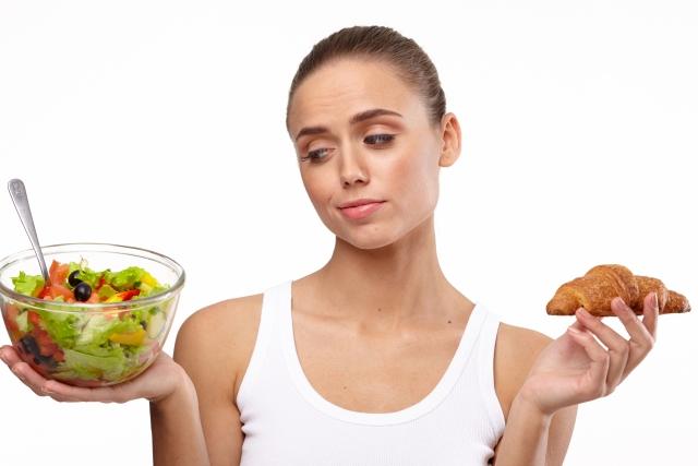 サラダとパンを持つ女性